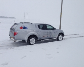 an its electrical pickup truck driving in the snow