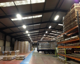 a warehouse with crates and roof lighting